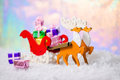 Christmas decoration reindeer and Santa sleigh with gifts in snow on north polar light background, closeup Royalty Free Stock Photo