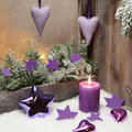 Christmas decoration in violet or purple with wood and a candle country style natural pine Stock Image