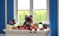 Christmas decoration at the window side with teddy bear candles presents and santa claus dolls Stock Photo