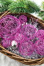 Christmas decorations in a basket and branch of spruce pink Stock Photos