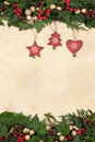 Christmas decorations floral background border with wooden and gold bauble holly ivy and mistletoe on old parchment paper Stock Images