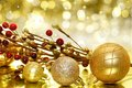 Christmas decorations golden baubles and branches with twinkling gold background Royalty Free Stock Images