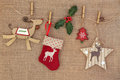 Christmas decorations old fashioned hanging on a line with holly over hessian background Royalty Free Stock Images