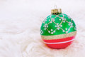 Christmas decorations a red and green ornament resting in soft white fur Stock Images