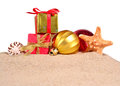 Christmas decorations seashells and starfish on a beach sand on Royalty Free Stock Photo
