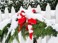 Christmas decorations in snow evergreen boughs with red ribbon hanging on white picket fence and covered with Stock Photography