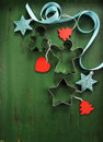 Christmas decorations on vintage green wood background, with cookie cutters - vertical. Royalty Free Stock Photo