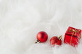 Christmas decorations on white fur red ornaments snowy fake nestled in lower right corner with copy space to the left and above Royalty Free Stock Photo