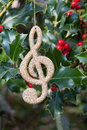 Christmas decorative music note hanging on holly sprigs manual focus Stock Photos