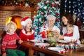 Christmas dinner. Family with kids at Xmas tree. Royalty Free Stock Photo