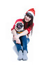 Christmas dog funny and cute friends – pretty girl and her pug pet – wearing red santa claus caps having fun smiling with Stock Photos