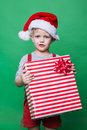 Christmas Elf holding big red gift box with ribbon. Santa Claus helper Royalty Free Stock Photo