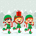 Christmas elves carrying presents santa helpers on snow background Royalty Free Stock Photos