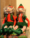 Christmas elves a pair of sitting on a shelf they are wearing traditional red and green colors Stock Photography