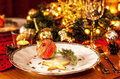 Christmas eve dinner party table setting with decorations lights and gold glittering elegant white plate close up Royalty Free Stock Photos