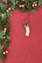 Christmas eve floral border with retro stocking bauble holly mistletoe ivy and cedar leaf sprigs over red mottled background Stock Image