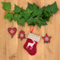 Christmas eve symbols of red stocking tree star and heart with ivy leaf sprigs over oak background Stock Photos