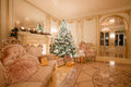 Christmas evening by candlelight. classic apartments with a white fireplace, decorated tree, bright sofa, large windows Royalty Free Stock Photo