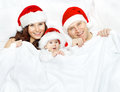 Christmas family and baby in santa claus hat over white red lying background covered by blanket Royalty Free Stock Image