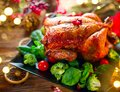 Christmas family dinner. Roasted chicken on holiday served table, decorated with gifts and burning candles. Roasted turkey Royalty Free Stock Photo
