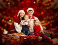 Christmas family four persons mother father children red of kids happy smiling over background Royalty Free Stock Photos
