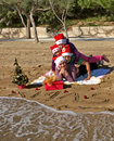 Christmas family laying on sand beach Stock Photos