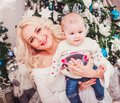 Christmas family, mother and baby smiling near the Xmas tree. Royalty Free Stock Photo
