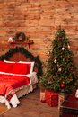 Christmas fir and the bed. New Year interior of room with bed and Christmas tree.