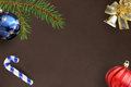 Christmas fir branch, stick, blue and red balloon and decorative bell on dark background Royalty Free Stock Photo