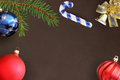 Christmas fir branch, stick, blue and red wavy balloon and decorative bell on dark background Royalty Free Stock Photo