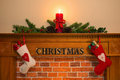 Christmas fireplace with stockings and candle mantelpiece red fresh garland made from holly two full of gifts hanging over the the Royalty Free Stock Image
