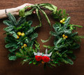 Christmas floral wreath decoration with baubles, red bow, holly and winter greenery over oak background. Royalty Free Stock Photo