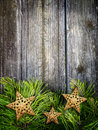 Christmas frame with stars bright green pine branches the bottom portion of an old textured wooden background golden decorate the Stock Photography