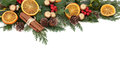 Christmas fruit border floral with dried orange and cinnamon spice baubles and winter greenery over white background Stock Image