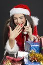 Christmas fun radiant young lady dressed in santa costume enjoying a funny conversation on phone against dark background hand on Royalty Free Stock Images