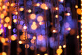 Christmas garland lights background blurred with golden and violet colors Royalty Free Stock Photos