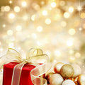 Title: Christmas gift and baubles on golden background