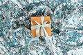 Christmas gift box against turquoise bokeh background.