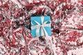 Christmas gift box against turquoise bokeh background.