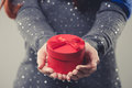 Christmas gift box beautiful small round red festive cradled in the cupped hands of a woman wearing a spangly top twinkling in the Stock Image