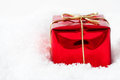 Christmas gift box in snow a single shiny red foil wrapping and tied to a bow with gold string ribbon nestled artificial white Royalty Free Stock Images