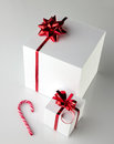 Christmas gift boxes and candycane white with red bright bow on grey light backlground Stock Image