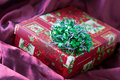 Christmas gift closeup shot of festive present in purple silk cloth Stock Photography