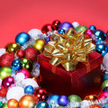 Christmas gift with gold bow and colorful balls over red background decorations holiday card Royalty Free Stock Images