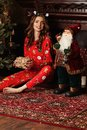 Christmas Gift. Happy Surprised Woman with brunette curly hair , dressed in a Christmas suit, opening Gift box at home. Christmas