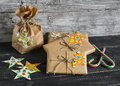 Christmas gifts in kraft paper with a homemade tag on a dark wooden surface. Royalty Free Stock Photo