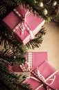 Christmas gifts in pink wrapping gift boxes branches and around base of decorated tree wrapped gingham ribbon and tied with bows Stock Photography