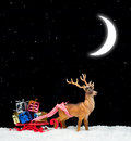 Christmas gifts on sledge red with gift boxes and reindeer at night Stock Photos