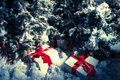 Christmas gifts wrapped with red ribbon under fake evergreen trees covered by snow Royalty Free Stock Photos