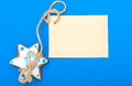 Christmas gingerbread cake star with icing and decoration and blank card homemade blue paper copy space on blue as background Stock Photo